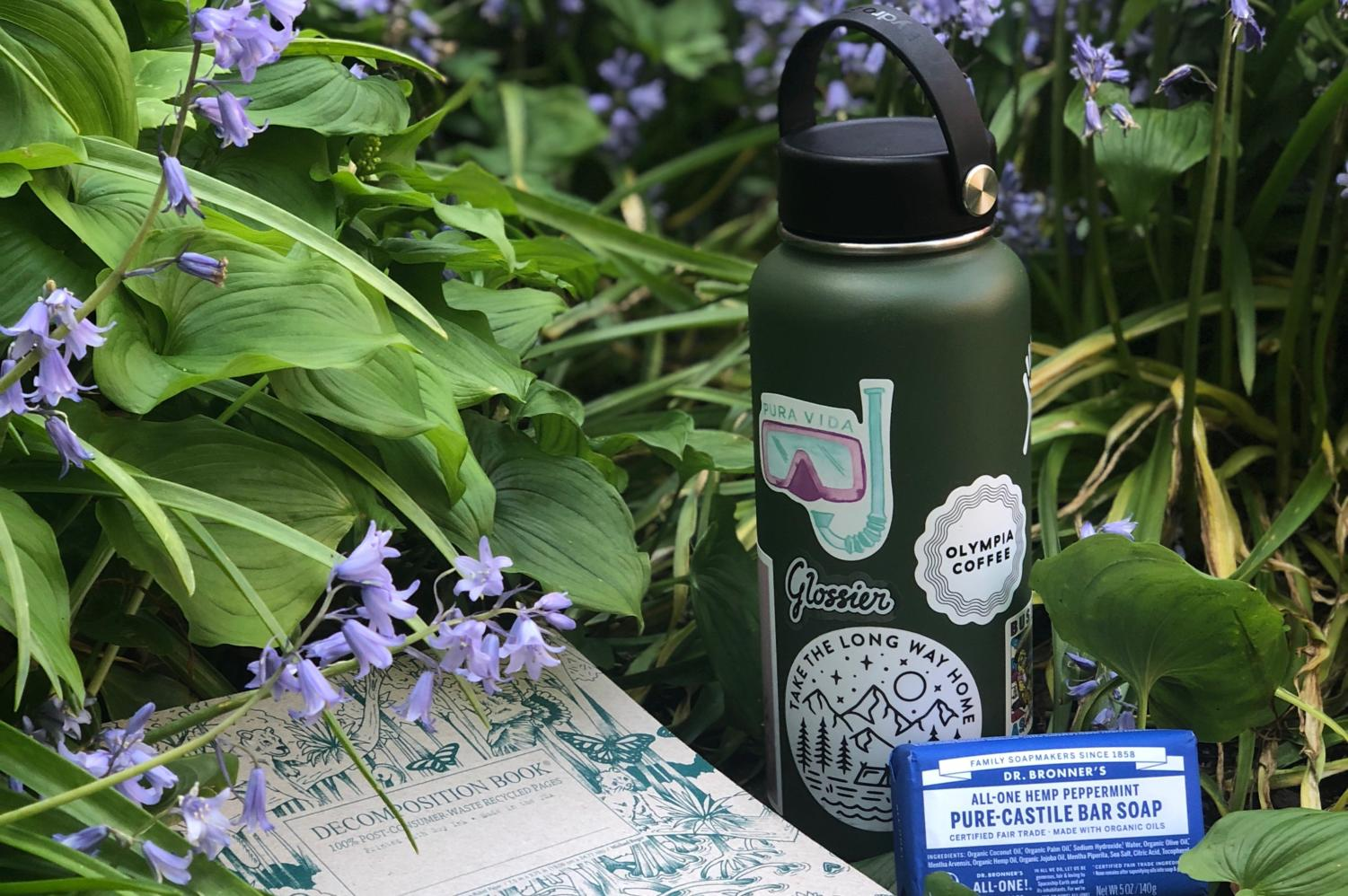 A decomposition notebook, Hydroflask and Dr. Bronner's bar soap are three environmentally friendly products.
