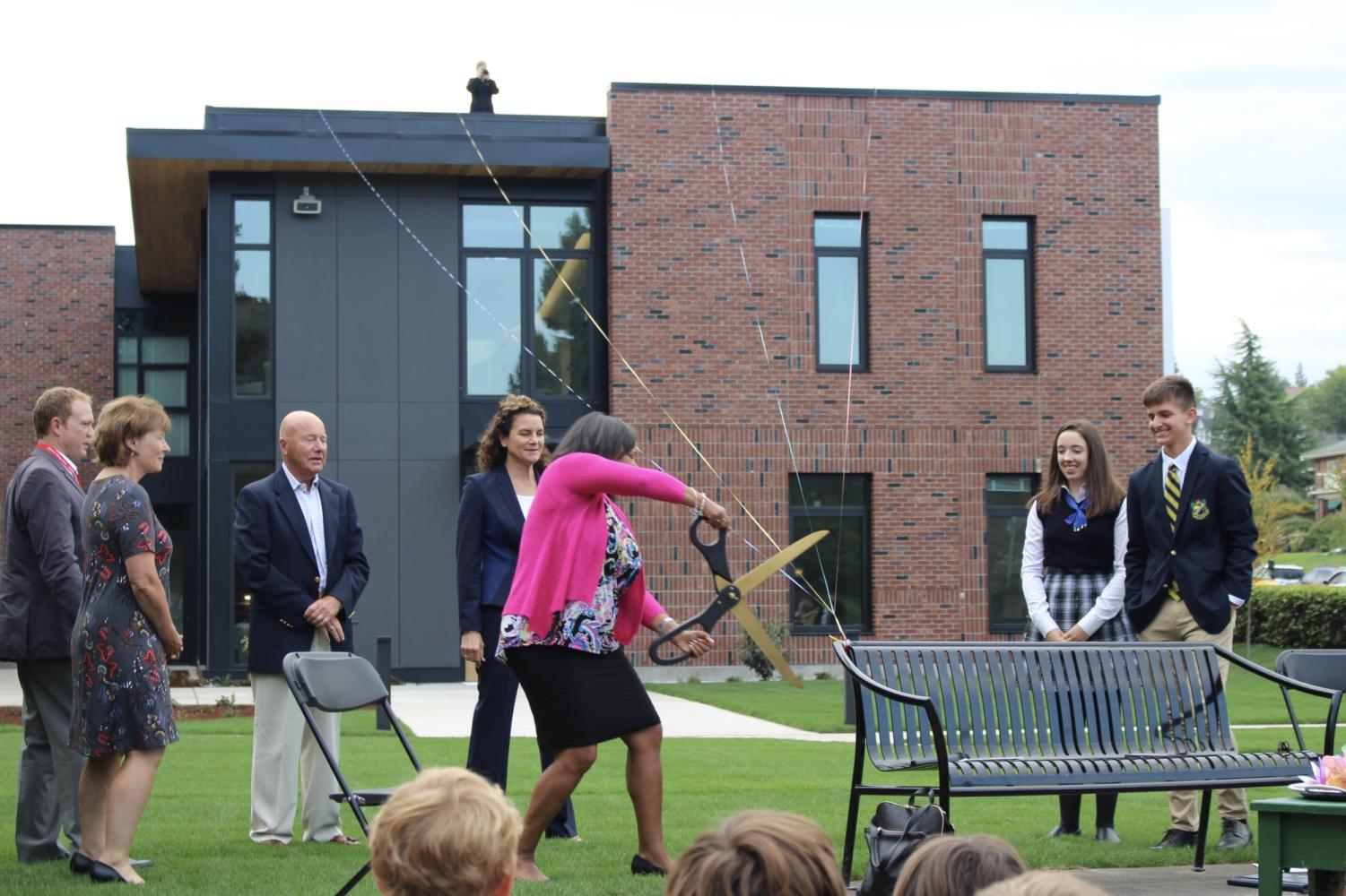Tacoma Mayor Victoria Woodards cuts the ribbons, representing Annie Wright's four tie colors, officially opening the new Upper School for Boys building.